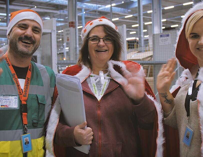 """3 Mitarbeiter winken in die Kamera, alle tragen eine rote Zipfelmütze. Der rechte Mitarbeiter trägt ein Band mit Aufschrift """"Betriebsrat""""."""
