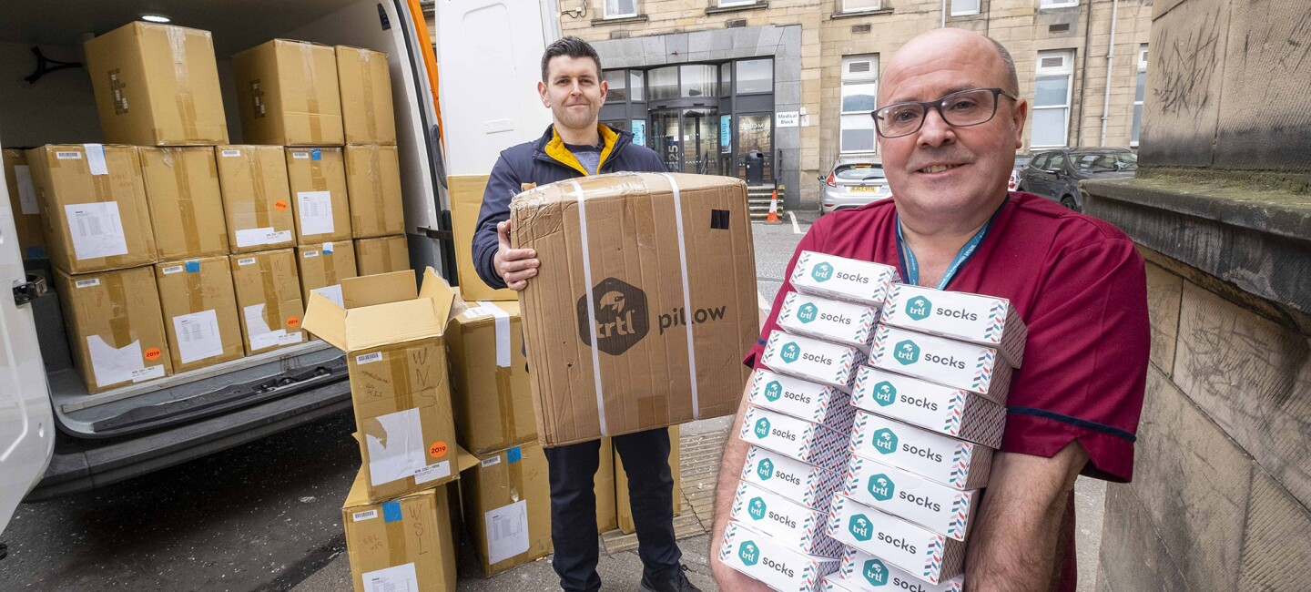 An image of the trtl team donating boxes of their products to key workers. They are holding stacks of boxes which they are unloading from a van.