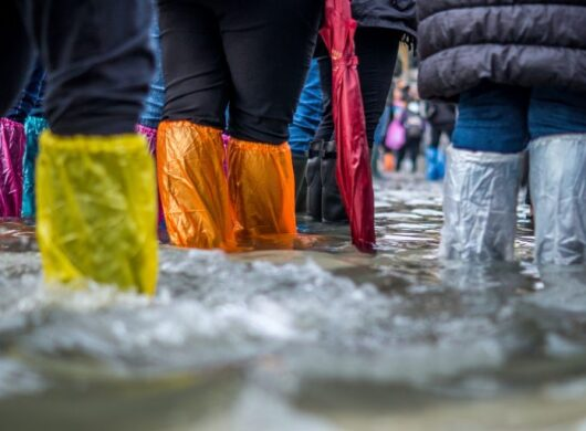 People stand shin-deep in floodwaters with protective plastic around clothing.