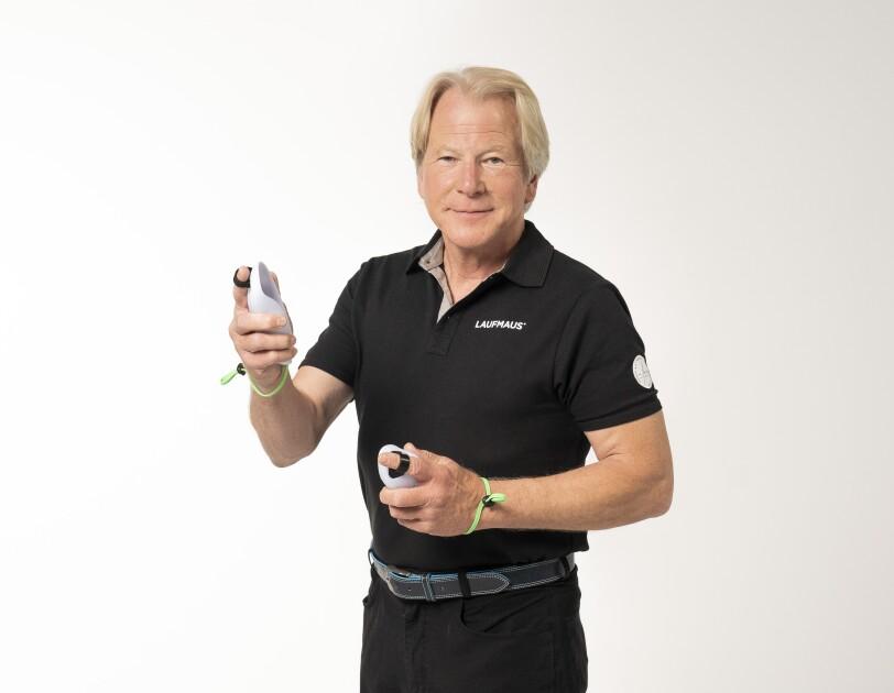Ein Mann mit grauen Haaren und einem schwarzen T-shirt lächelt in die Kamera.