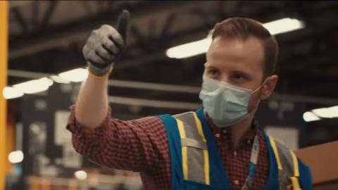 Mitarbeiter im Logistikzentrum trägt einen Mundschutz. Er sieht glücklich aus und hält seinen Daumen hoch.