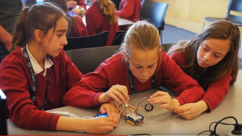 Three girl students in red school uniforms are trying to connect wires during the AWS student workshop in Madrid, Spain.