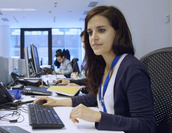 Ritratto di Nadia Cazzamali, Account Manager Marketplace di Amazon. E' seduta alla sua scrivania e guarda a uno dei due schermi che ha di fronte. Sullo sfondo, alla sua destra, due suoi colleghi e le finestre dell'ufficio.
