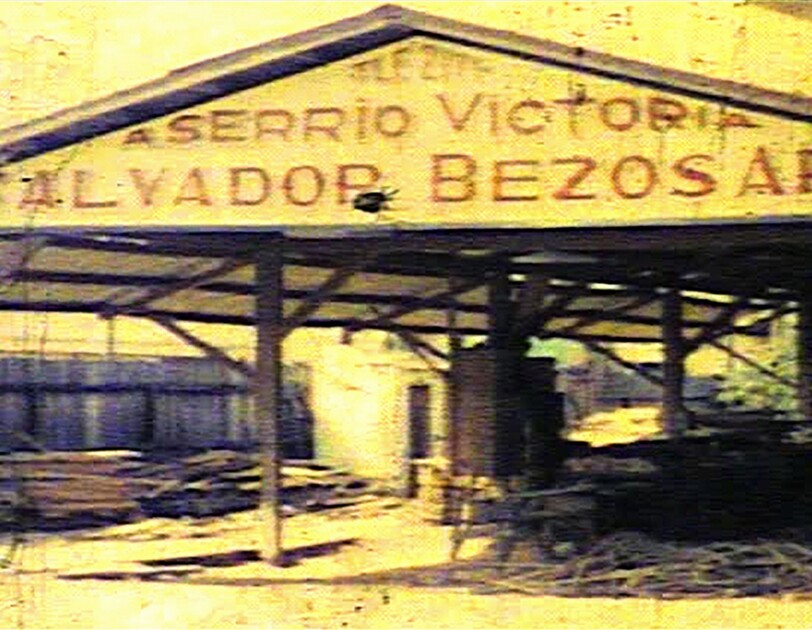 """Vintage image of a lumber mill. The painted sign on the building includes the family name """"Bezos."""""""