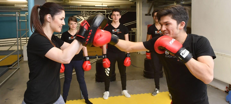 """Jugendliche stehen im Boxring. Ein Junge und ein Mädchen boxen miteinander. Die anderen stehen drumherum und schauen zu. Sie tragen schwarze T-Shirts mit der Aufschrift """"Boxt euch durch München"""" und rote Boxhandschuhe."""
