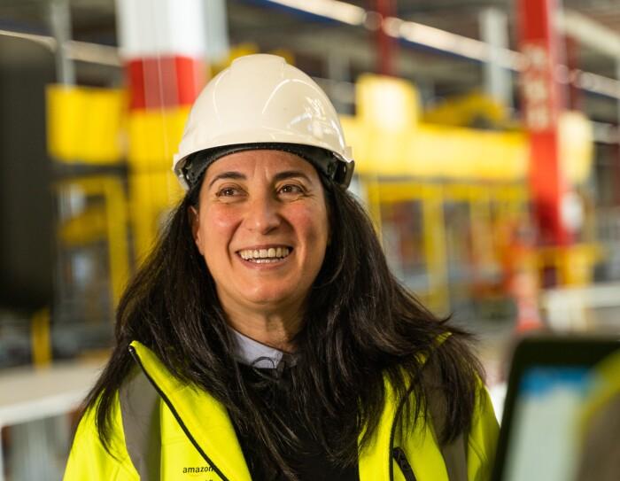 Sonia Corvera, Responsable Senior de Construcción para Amazon España, en primer plano y sonriendo con casco y chaleco amarillo. En un momento de la grabación.