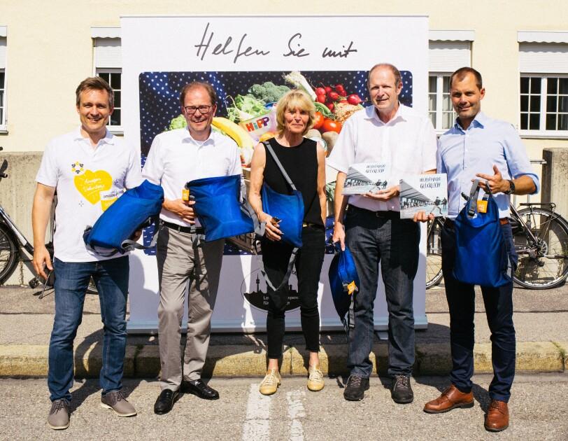 """Gruppenbild vor einem Plakat mit der Aufschrift """"Helfen sie mit"""". Alle Abgebildeten halten blaue Schulbeutel in der Hand."""
