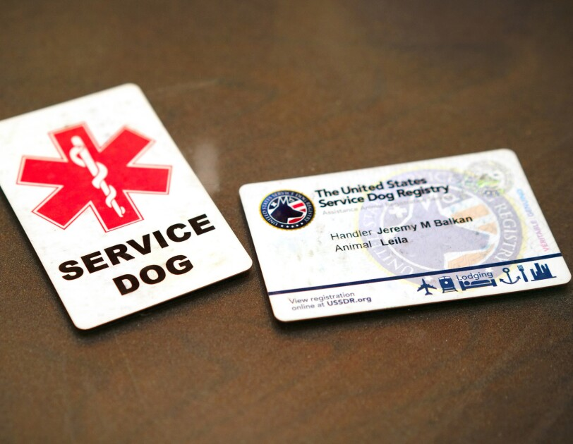 "Two cards on a table. One is marked ""SERVICE DOG."" The other is issued by the United States Service Dog Registry."
