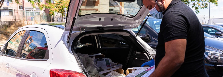Colaborador de Amazon Flex introduciendo una caja de comida dentro del coche. El coche es de color gris y tiene el capó abierto. UN colaborador de Amazon Flex con mascarilla, guantes y reloj, pelo negro corto y barba introduce dentro del maletero una caja blanca con flores rojas que dentro tienes bolsas de comida. El coche está aparcado en un garaje exterior.