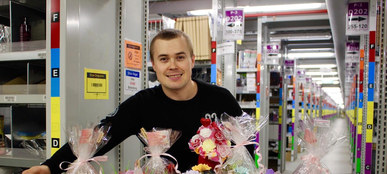 Juraj steht im Logistikzentrum, vor ihm eine bunte Palette an Seifensträußen