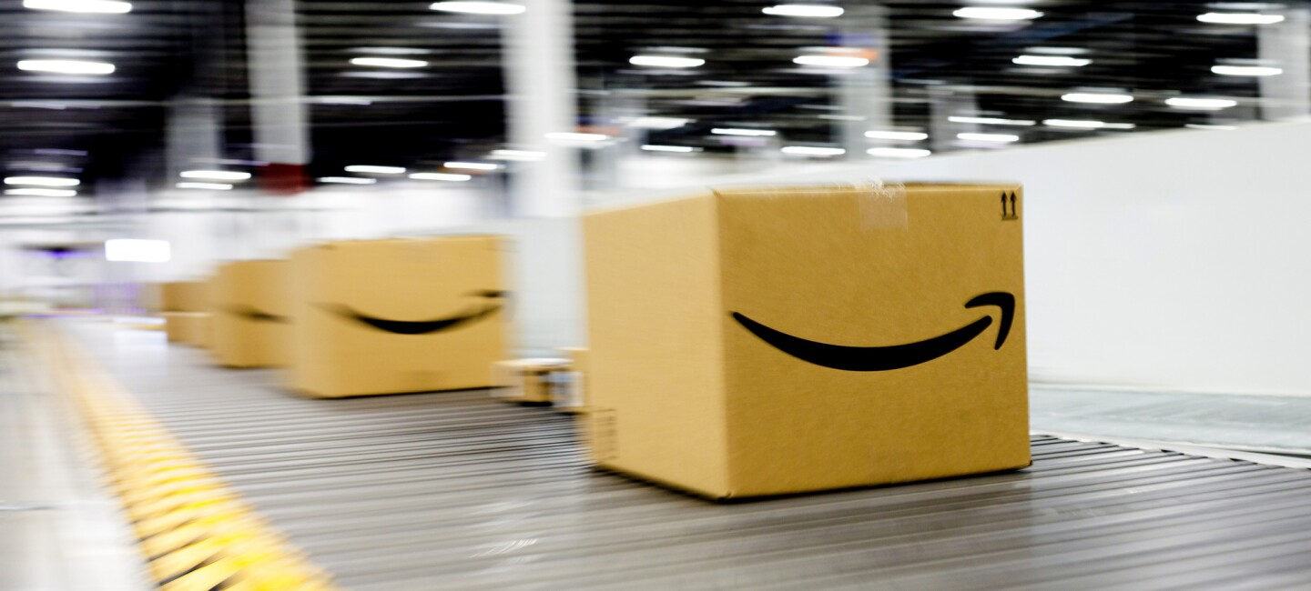 Amazon smile boxes move move along a conveyor belt within an Amazon Fulfilment Center or warehouse.