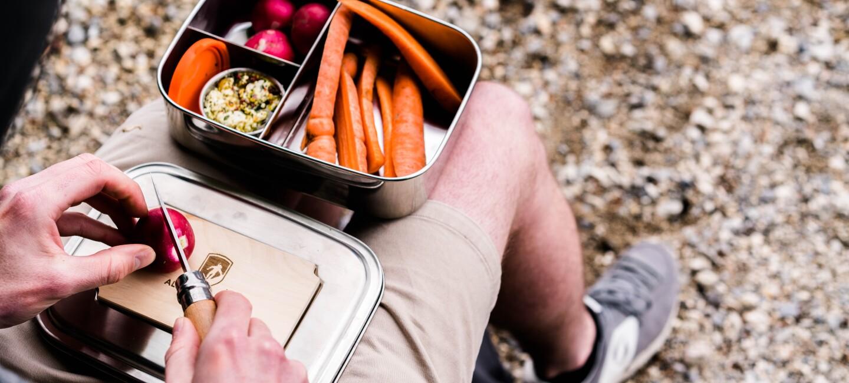 Ein Mann schneidet Gemüse auf dem Deckel einer Brotzeitbox. Der Deckel und die Brotbox liegen auf seinem Schoß. Die Brotbox ist bereits mir Karotten und Radieschen gefüllt.