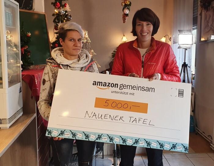 Katrin Gille (links) von der Nauener Tafel nimmt die Spende des Amazon Logistikzentrums in Brieselang von Standortleiterin Sylvia Reichardt entgegen.