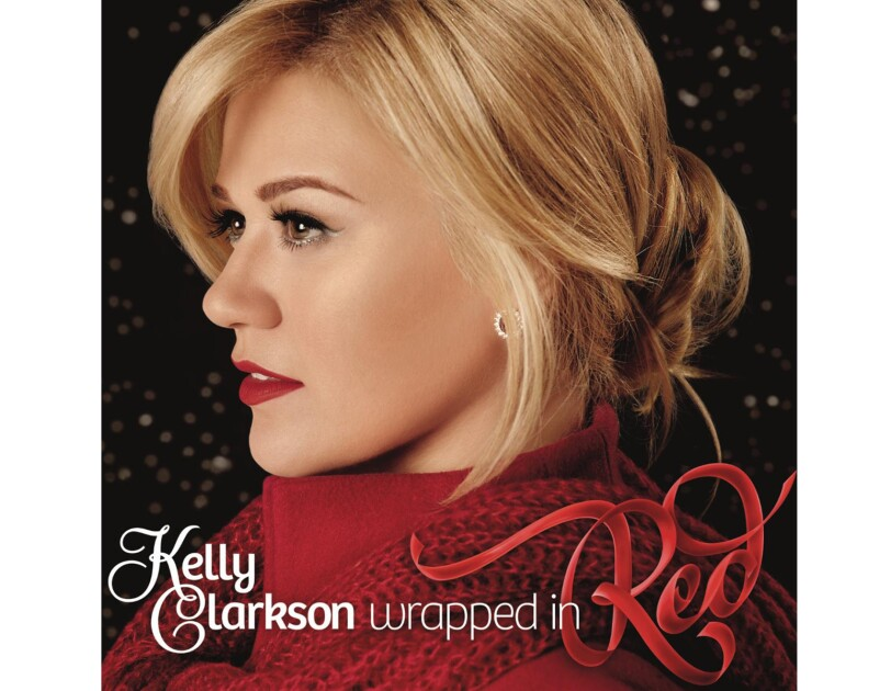 Kelly Clarkson wears her blonde hair tied behind her head, a red high-collared shirt with red scarf around her shoulders. Silver earrings, eye liner, and red lipstick completes her look. She looks to her right.