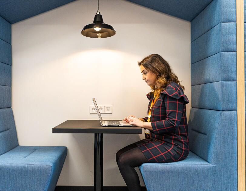 Elena Bris trabajando en las oficinas de Amazon en Madrid.  Está sentada en una mesa negra, trabajando en el ordenador. Está sentada en un sofá azul claro que tiene forma de pentágono. Así que ella queda dentro del  pentágono. Elena lleva un bagde con una cinta de color amarillo y un vestido azul con cuadros de color rojo. Es un vestdo por encima de la rodilla. Tiene el pelo largo y ondulador. Lleva pendientes y los ojos pintados de azull.