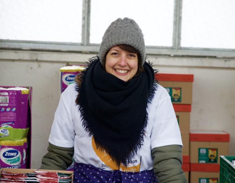 Eine junge Frau bei der Ausgabe von Lebensmitteln: Sie trägt eine graue Wollmütze und ein schwarzes Wolltuch unter dem das Amazon-Volunteers-T-Shirt zu sehen ist.