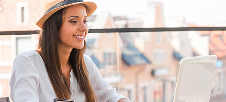 Donna guarda il suo computer seduta di fronte a un tavolo, all'aperto su una terrazza. Indossa un cappello di paglia e accanto al suo braccio destro tiene una tazza di caffè.