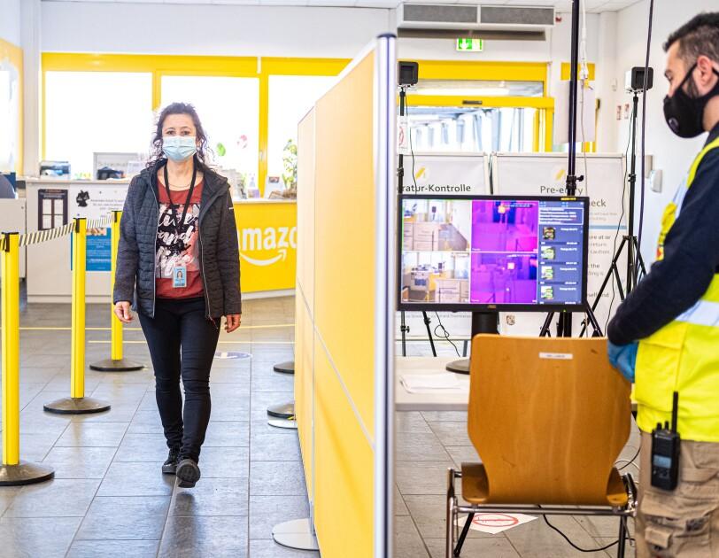 Eine Mitarbeiterin betritt das Logistikzentrum. Dabei wird kontaktlos Fieber gemessen