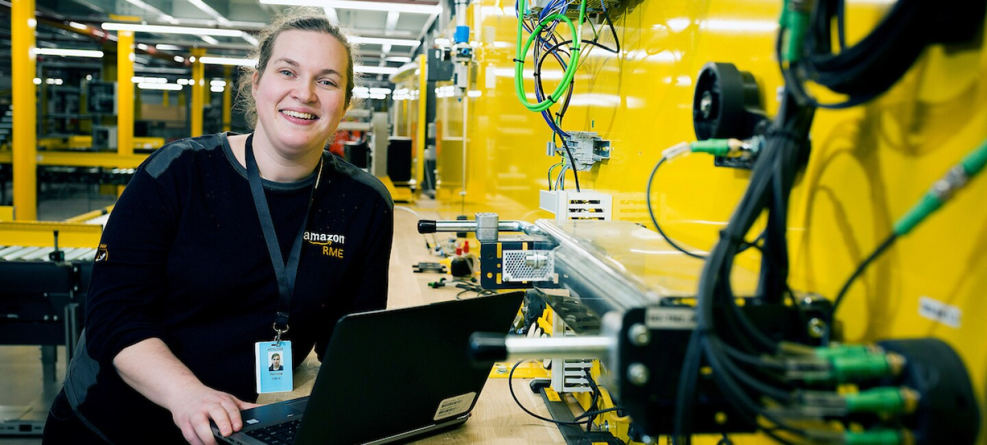 Apprentice, Nicola Elliot, pictured with her laptop smiling at the camera. There is warehouse machinery in the background.