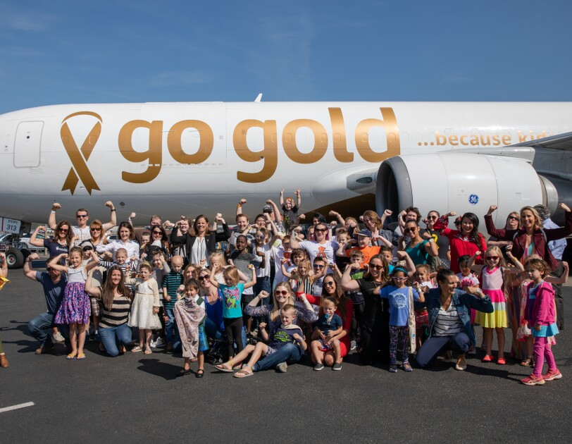 Dozens of children and their parents stand in front of a #GoGold branded Amazon Air plane. Most people in the photo are flexing their arm muscles to signify strength.