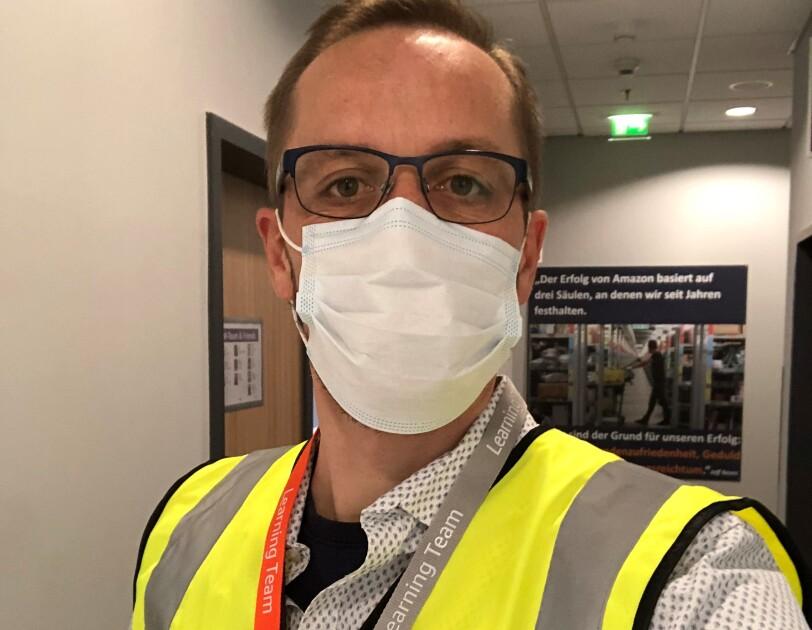 Ein Mann mit blonden Haaren, Brille und Sicherheitsweste vor einer Packstation im Logistikzentrum