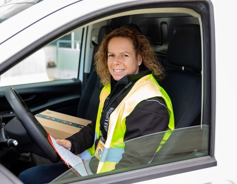 Eine Frau mit halblangen Haaren und Sicherheitsweste in einem Lieferfahrzeug am Steuer.