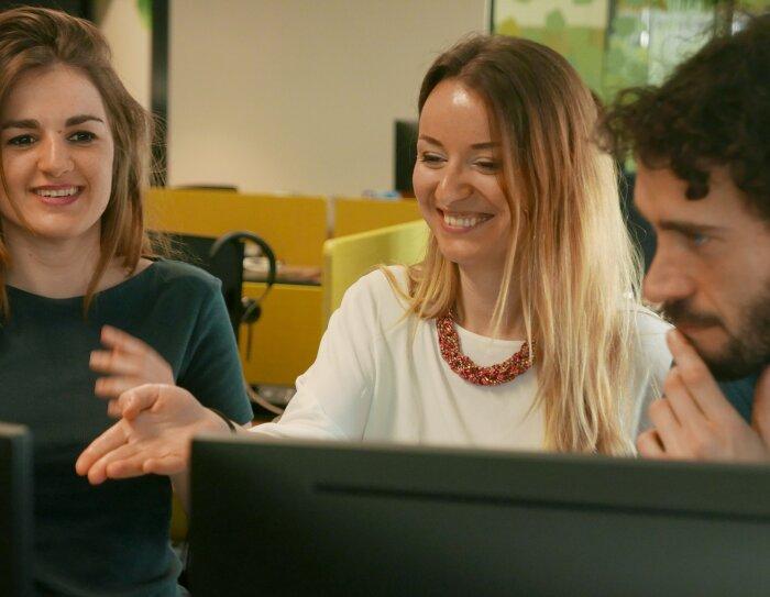 Dos mujeres y un hombre, todos de unos treinta años. Las dos mujeres están sonriendo mirando una pantalla de ordenador y el hombre, con la mano apoyada en su barbilla, observa la pantalla.