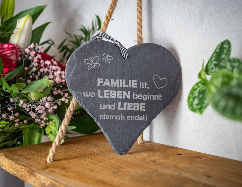 """Auf einem Regal steht ein Herz aus Stein mit der Aufschrift """"Familie ist, wo Leben und Lieben niemals endet""""."""