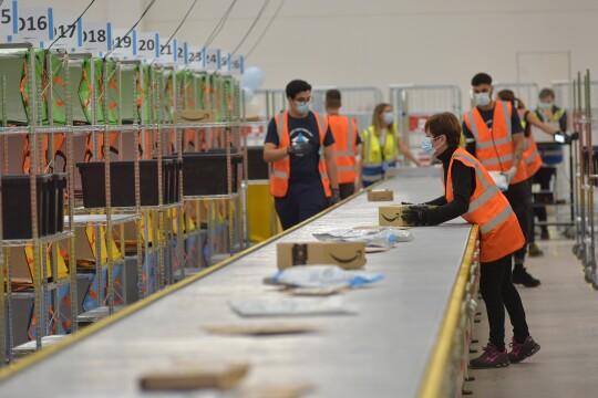 Un rullo portapacchi in un magazzino Amazon. Scatole si alternano a buste in carta. Si vedono in secondo piano alcuni dipendenti del magazzino.