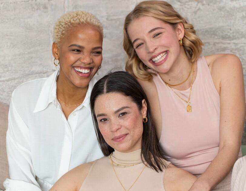 Drei Frauen sitzen auf einem Sofa und lachen in die Kamera.