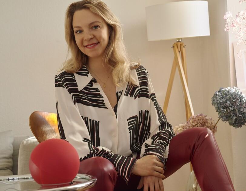 Eine Frau mit blonden Harren sitzt auf einem Stuhl und trägt eine weiß-schwarze Bluse. Sie lächelt in die Kamera.