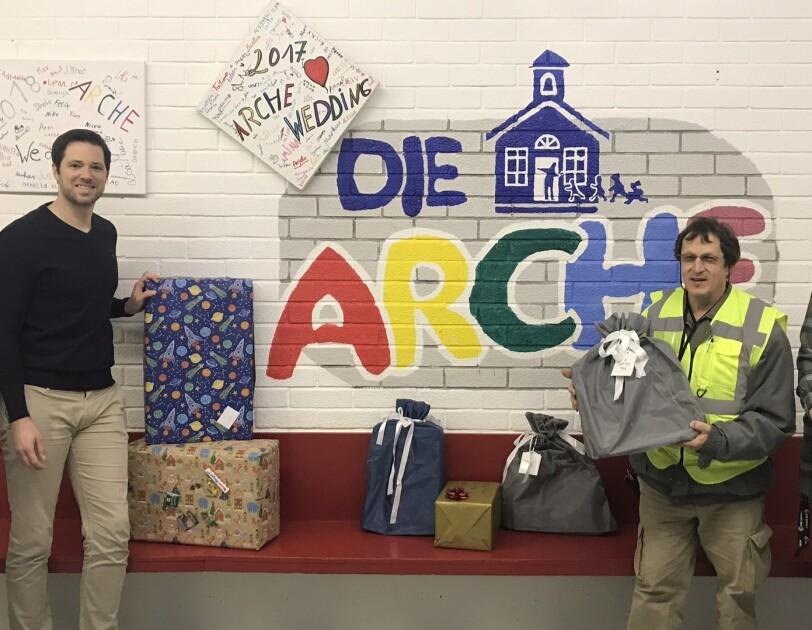 MitarbeiterInnen stehen mit Geschenken vor dem Logo der Arche.