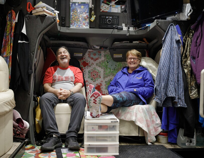 A man and woman sit in matching chairs inside their motorhome. The man is laughing, and the woman is smiling.