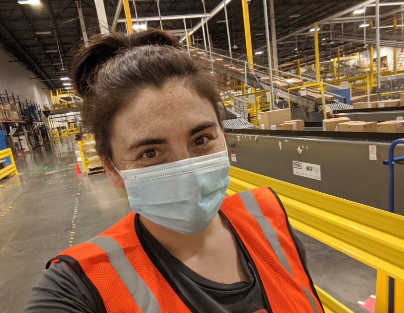 Sarah Freeman, an Amazon associate, is smiling for a selfie inside the Amazon fulfillment center where she works. She is wearing a mask and other Amazon safety gear like an orange vest.