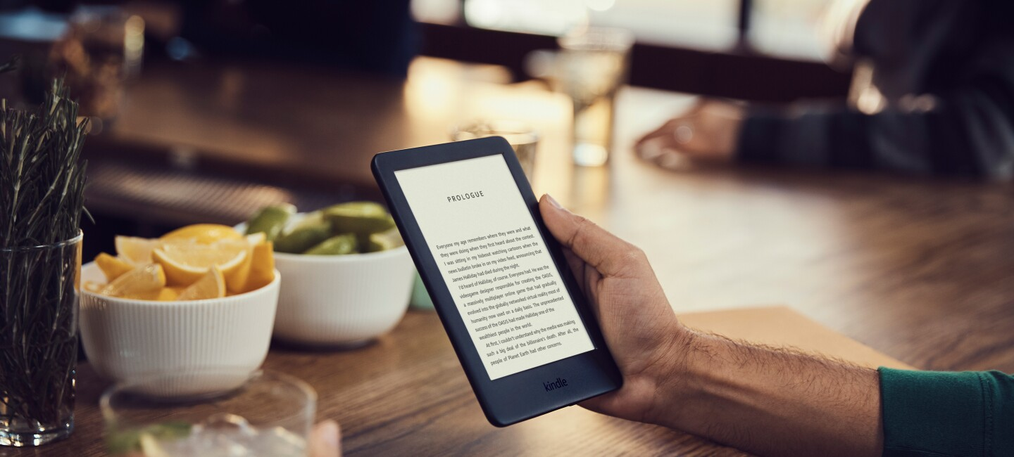 A man holds a Kindle device in his right hand, reading the prologue of a book. He holds a cocktail in the right hand, in a bar setting.