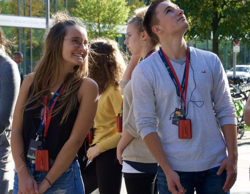 4 Jugendliche stehen vor dem Amazon Gebäude und blicken in eine Richtung