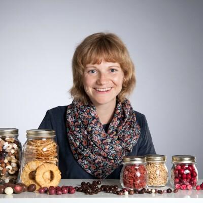 Frau mit kurzen Haaren sitzt vor einem Tisch, auf dem Einmachgläser mit getrocketen Früchten stehen