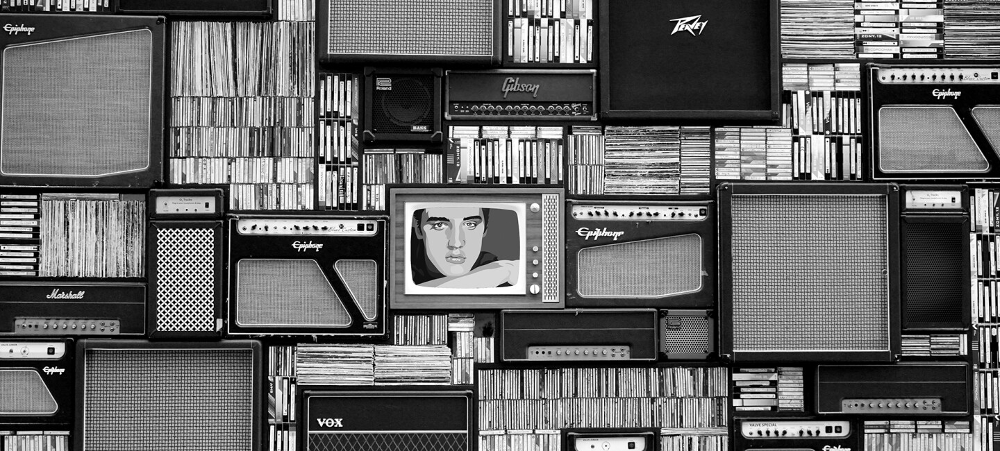 A wall of records, cassette tapes, speakers, and a photo of Elvis Presley.