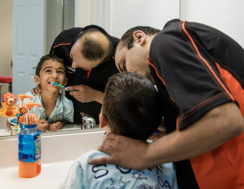 A man brushes a young boy's teeth in a bathroom.