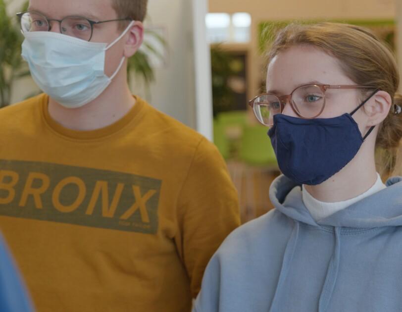 Ein Mann und ein Mädchen schauen gemeinsam auf einen nicht-sichtbaren Punkt Sie tragen beide eine Mund-Nasen-Bedeckung.