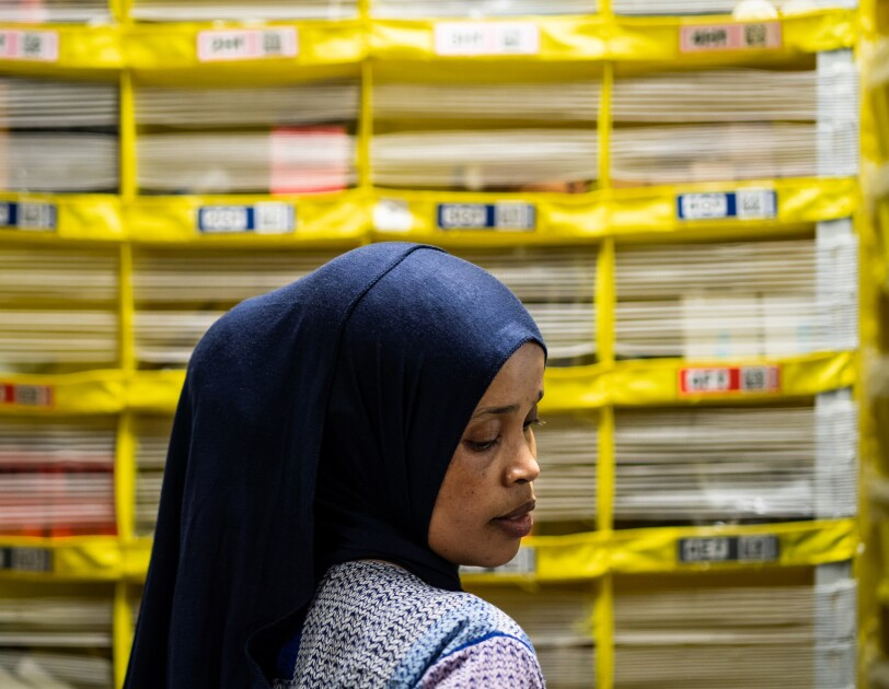 A woman is protographed in profile. Yellow shelving units are behind her. She wears a scarf on her head.