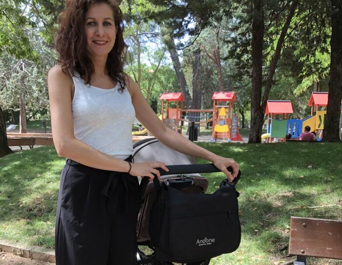 Irene posa de pie sujetando un carro de bebé que tiene su bolso, Andone Dynamic Walks. Mira a cámara sonriendo y va vestida con una camiseta blanca sin mangas y una falda larga. Está en un parque y en el fondo se puede ver una zona de juegos infantil.