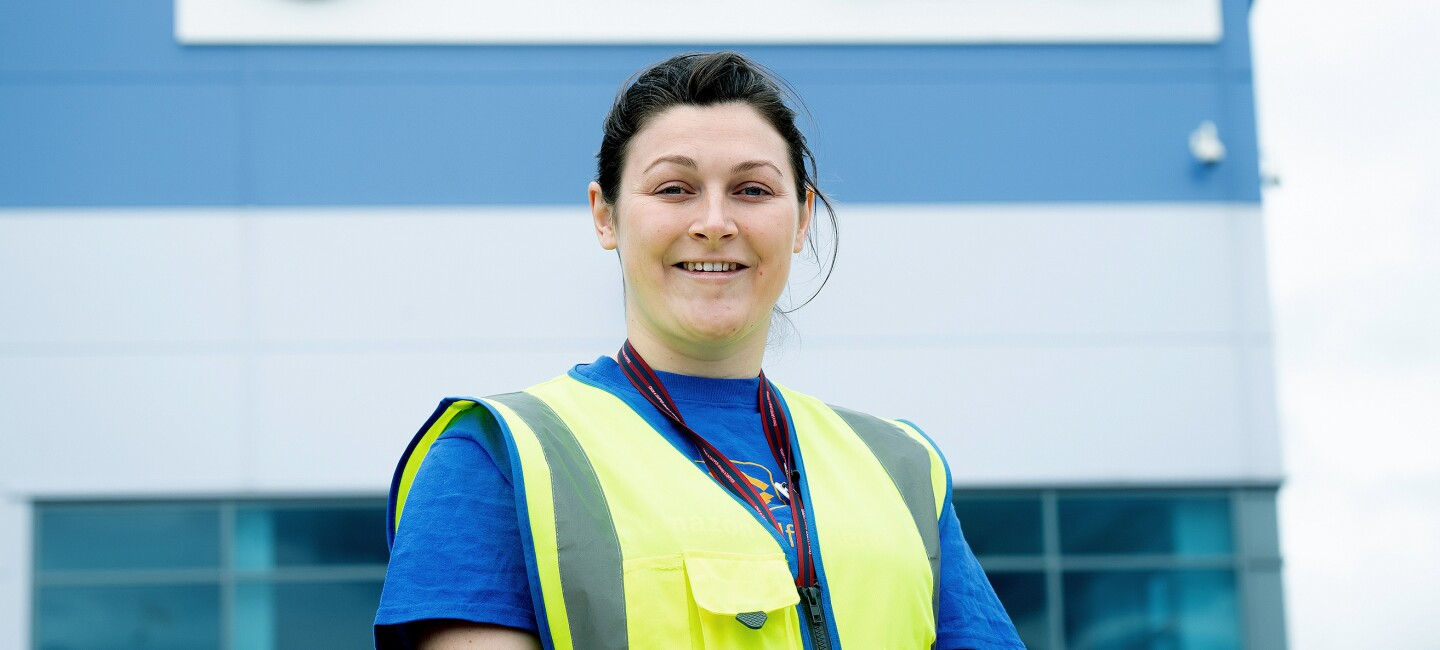 Sophie Martin smiling with a high visibility vest on, outside an Amazon fulfilment centre