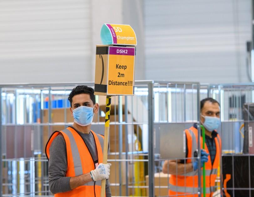 """Ein Mitarbeiter in Sicherheitsweste mit einem Schild: """"Keep 2 m Distance!"""""""