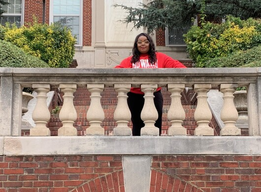"A student photographed on a college campus. She wears a red sweatshirt with the word ""Howard"" in white letters."