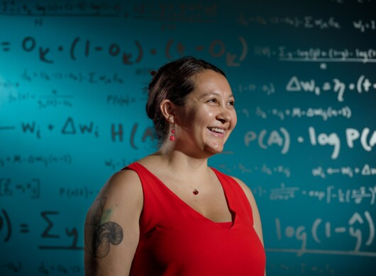 A woman in a red sleeveless top stands in from of a wall of mathematical equations.