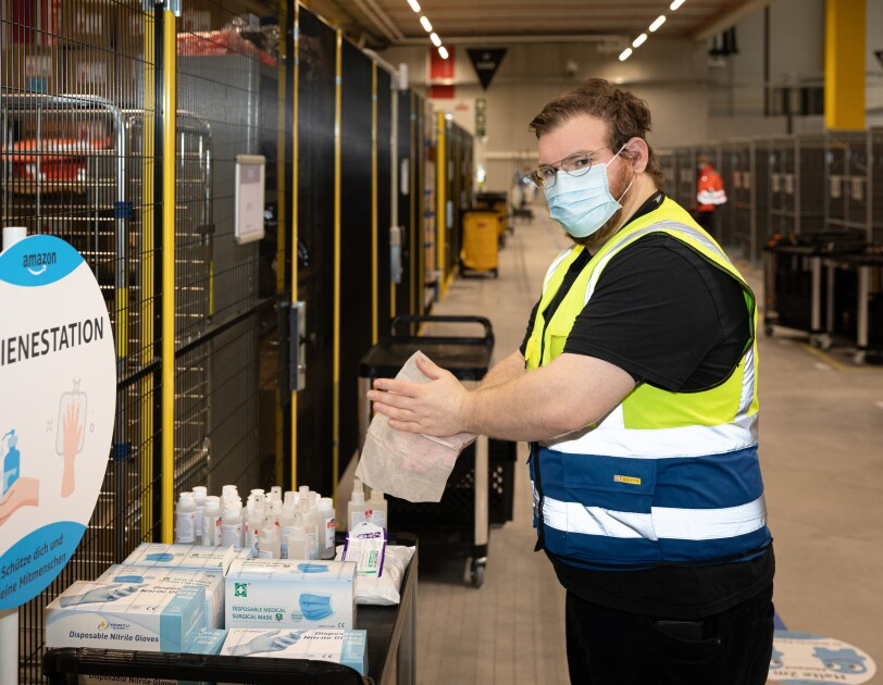 Ein Mitarbeiter an der Hygienestation beim Desinfizieren der Hände.