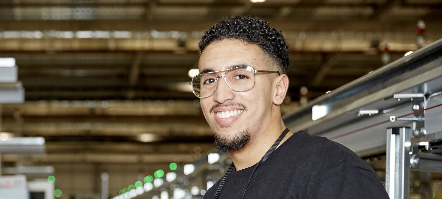 A close up photo of Imad smiling at the camera inside an Amazon warehouse