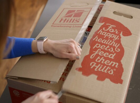 "A woman opens a recyclable Hill's Pet Food cardboard box that says, ""For happy, healthy pets, feed them Hill's."""