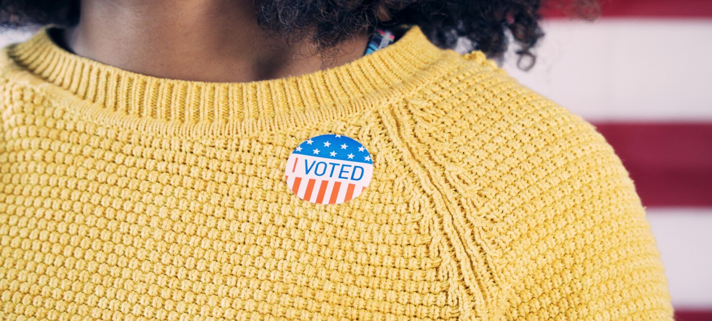 """A woman with brown skin and curly hair wears a yellow sweater. Upon that sweater, she wears a sticker that states, """"I VOTED"""" with white stars on blue background, and red and white stripes."""